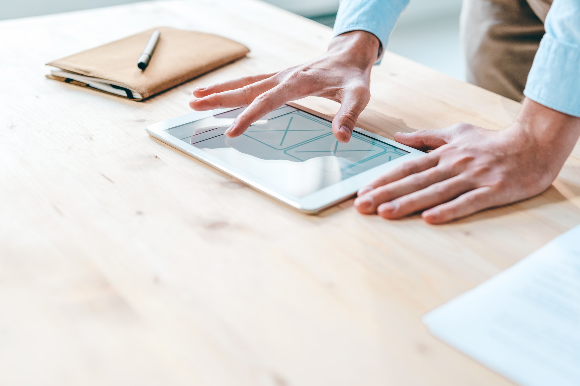 Young contemporary webdesigner pointing at application design on touchpad screen